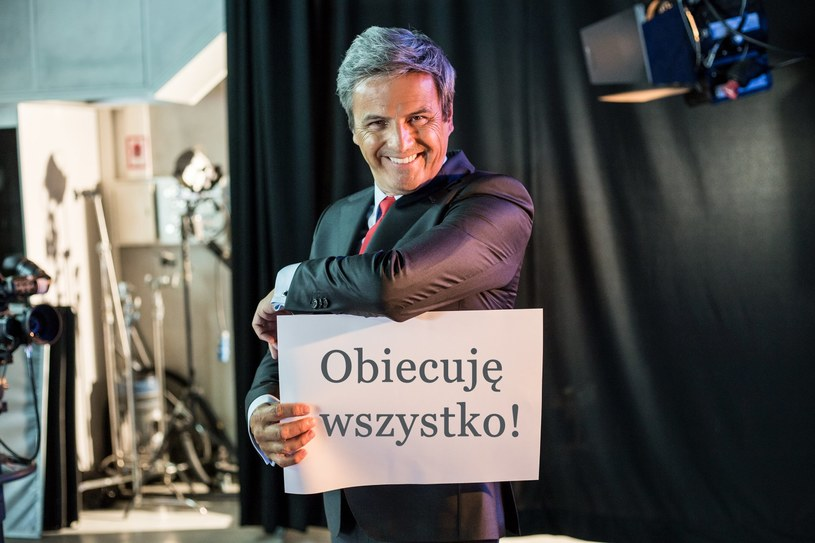 """W przededniu wyborów parlamentarnych producenci komedii """"Kochaj"""" postanowili przedstawić kandydata na... premiera! Piotr Polk reklamuje swoją kandydaturę hasłem """"Nowa partia, nowy premier, nowa jakość""""."""