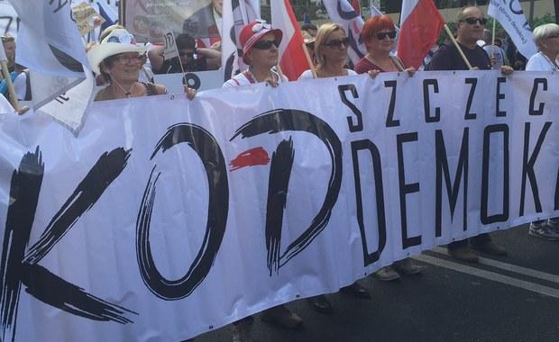 """Po godz. 15 przed siedzibą Trybunału Konstytucyjnego rozpoczęła się manifestacja Komitetu Obrony Demokracji. Odbywała się pod hasłem: """"Jedna Polska - dość podziałów"""". """"Zależy nam, żeby Polska była silną różnorodnością, ale połączoną wspólnymi wartościami"""" - mówił przed marszem szef KOD Mateusz Kijowski. Jak informował chwilę po 15 reporter RMF FM, na marszu jest kilkaset, może tysiąc osób. W kilkadziesiąt minut liczba ta zwiększyła się do kilku tysięcy manifestujących. Z czasem wzrosła do kilkunastu tysięcy. Według policji na marszu było 12 tysięcy osób. Między innymi dlatego też manifestacja wyruszyła spod Trybunału Konstytucyjnego z godzinnym opóźnieniem."""