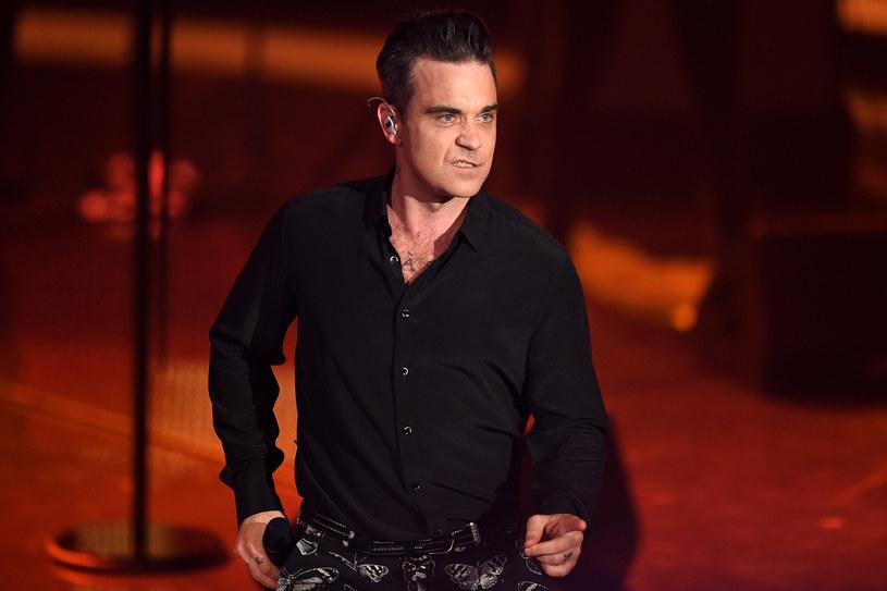 """Robbie Williams w trakcie sylwestrowego koncertu przybijał """"piątki"""" z publicznością, a następnie zdezynfekował ręce żelem antybakteryjnym. Jego zachowanie wywołało sporo kontrowersji. Wokalista odniósł się do sytuacji w żartobliwym filmiku opublikowanym na Instagramie."""