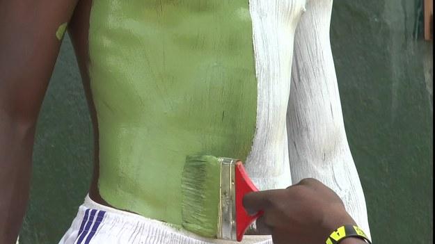 """Hasła reklamowe malowane bezpośrednio na ludzkim ciele? Takie """"żywe reklamy"""" stoją na ulicach stolicy Liberii. Biznes doskonale się rozwija. Reklamodawcy za prezentację trwającą 5 godzin płacą 50 dolarów. To uciążliwa praca, ale daje młodym bezrobotnym możliwość zarobkowania. """"Żywe posągi"""" wynajmują także parte polityczne."""
