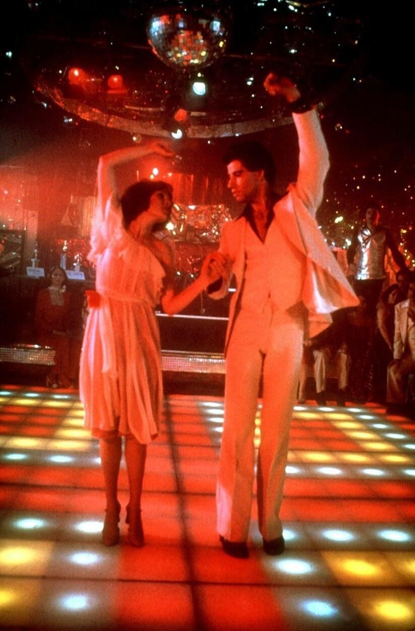 """Lśniący garnitur Johna Travolty jest najbardziej rozpoznawalnym kostiumem filmowym wszech czasów, a jego taneczny krok do dziś naśladują fani. Choć """"Gorączka sobotniej nocy"""" skończyła już 40 lat, wciąż jest wielkim przebojem."""