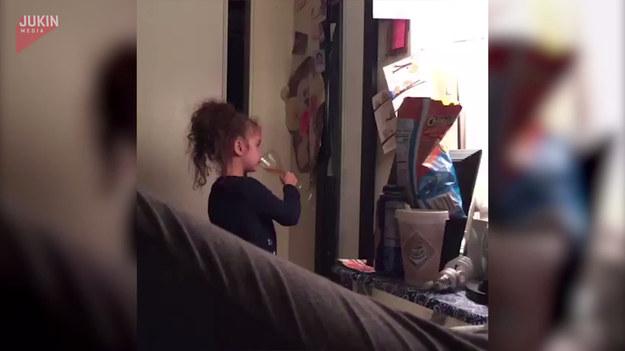Nagranie pokazujące śmieszną sytuację. Dziewczynka wznosi toast i brzdęka się szklankom wypełnionioną sokiem jabłkowym.