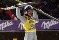 Adam Małysz podnosi narty w geście triumfu po zwycięstwie w Zakopanem