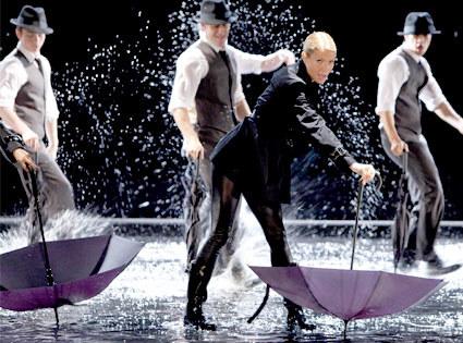 Aktorka tańczy, śpiewa i wymachuje parasolką