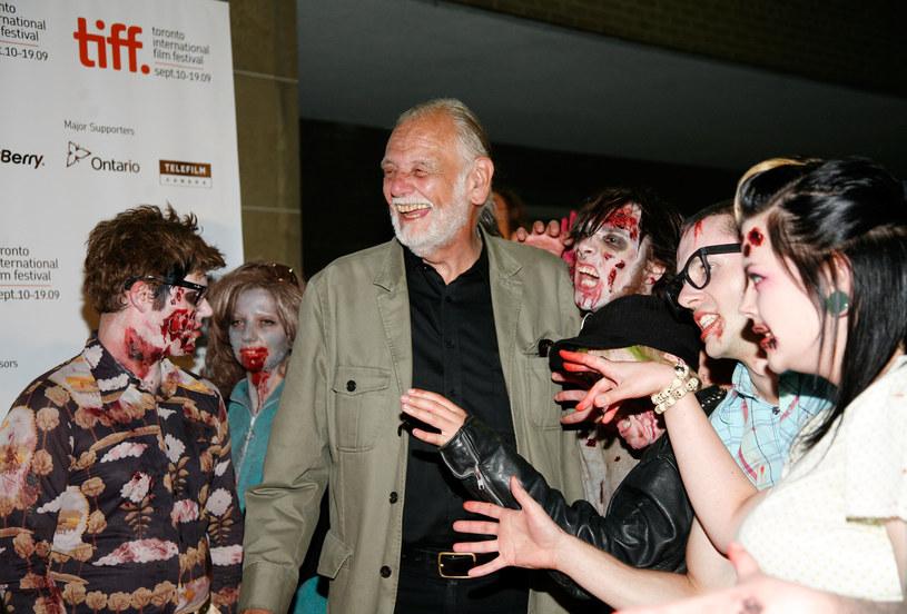 """""""Noc żywych trupów"""" dzięki estetyce nawiązującej do niemieckiego ekspresjonizmu, precyzyjnie budowanemu uczuciu osaczenia i przełamywaniu społecznych tabu (dziecko zmieniające się w zombie) zapisała się w historii kina jako jeden z najlepszych horrorów. Na zdjęciu George A. Romero w otoczeniu """"fanów"""" /Malcolm Taylor /Getty Images/Flash Press Media"""
