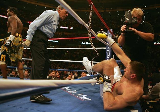 Andrzej Gołota poza linami ringu w przegranej po 53 sekundach walce z Lamonem Brewsterem /AFP
