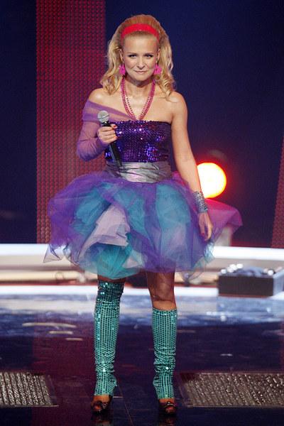 """Kolorowy wizerunek prezentowała także w programie """"Jak Oni śpiewają!"""". Jej sceniczne kostiumy balansowały na granicy groteski."""