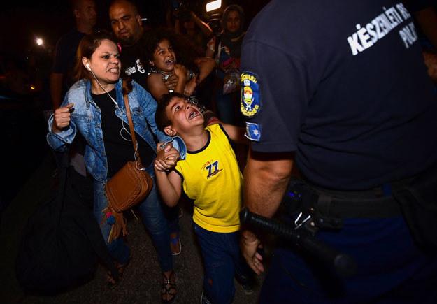 Bicske: Policjanci starają się przekonać uchodźców do udania się do obozu dla imigrantów /Attila Kisbenedek /AFP