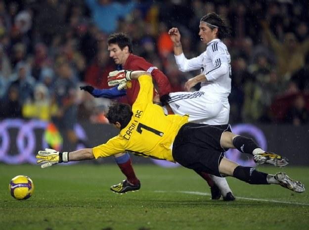 Bramkarz Realu Iker Casillas próbuje powstrzymać gwiazdę Barcelony Lionela Messiego /AFP