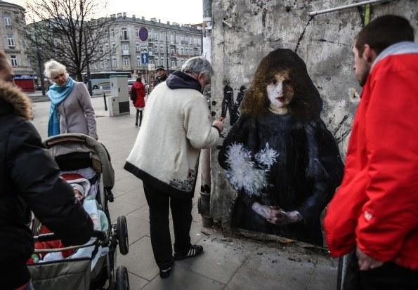 """Casabianca nakleja na ścianę jednej z kamienic """"Dziewczynkę z chryzantemami"""" Olgi Boznańskiej /PAP/Leszek Szymański /PAP"""