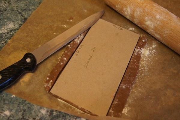 Mając szablony przygotowujemy ciasto: W garnku rozpuszczamy kostkę margaryny, 200 g cukru, 8 łyżek miodu, studzimy. Wsypujemy 600 g mąki, łyżkę kakao, 1,5 łyżeczki sody oraz paczkę przyprawy do piernika. Mieszamy łyżką, a następnie zagniatamy ciasto. Wałkujemy na grubość 0,5 cm ciasto na ściany boczne i cieco cieńsze na dach. Wykrawamy elementy używając gotowych szablonów.