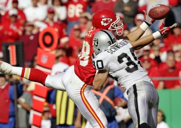 Chiefs - Raiders 27-23. Tony Gonzalez próbuje złapać pilkę atakowany przez Stuarta Schweigerta /AFP