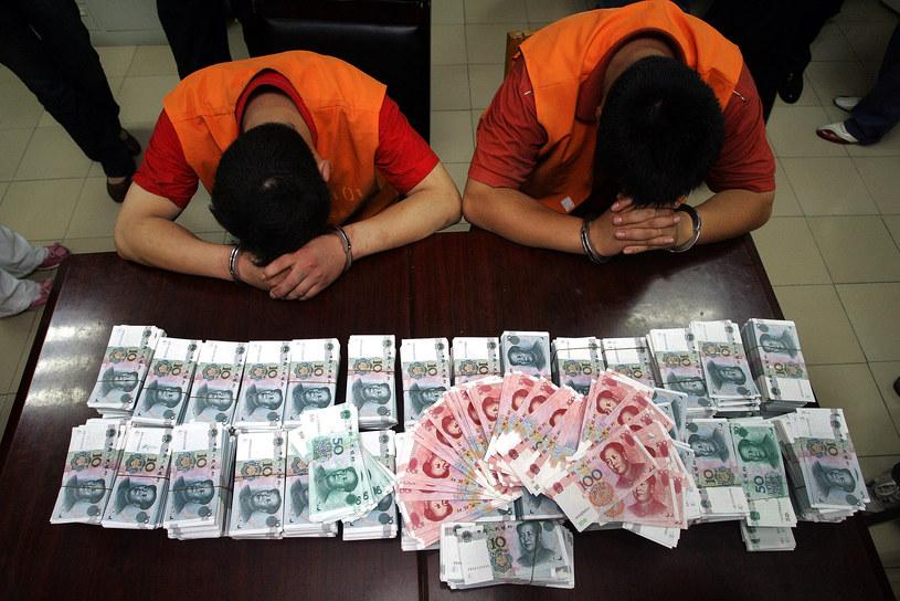 """Chińska policja """"prezentuje"""" dwie osoby zatrzymane pod zarzutem wprowadzania do obiegu fałszywych bankonotów /AFP"""