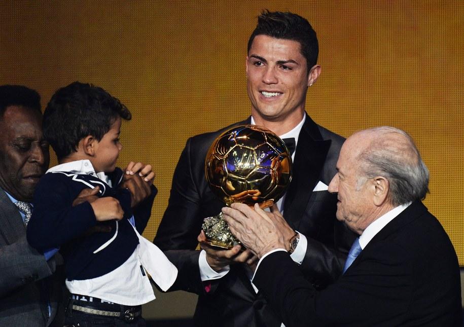 Cristiano Ronaldo odbiera Złotą Piłkę z rąk prezydenta FIFA Seppa Blattera. Na scenie pojawił się również syn piłkarza /STEFFEN SCHMIDT /PAP/EPA