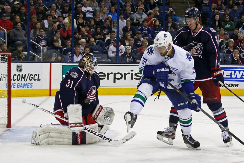 Curtis McElhinney, bramkarz Columbus Blue Jackets broni strzał Chrisa Higginsa (Vancouver Canucks) /AFP