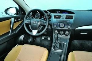 Czarna tablica przyrządów wygląda ponuro. Na szczęście jasna tapicerka ożywia wnętrze. /Mazda