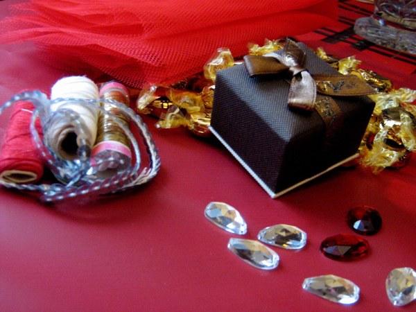 Materiały: drobny prezent (np. biżuteria), cukierki, ozdobna folia pakowna, pasek tiulu, sznurek cekinów (50 cm), nici, kilka kamieni akrylowych.