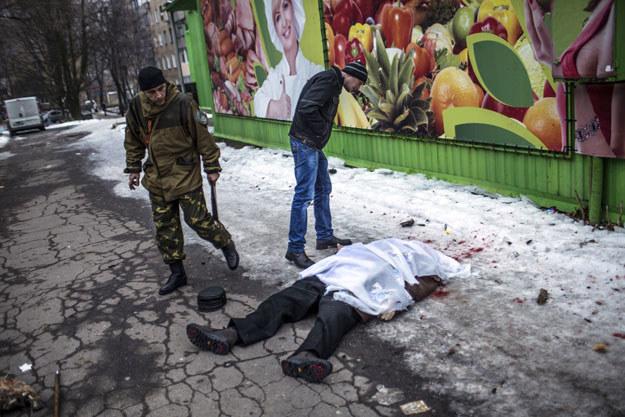 Donieck: Prorosyjski separatysta nad zwłokami cywila fot. Manu Brabo /AFP