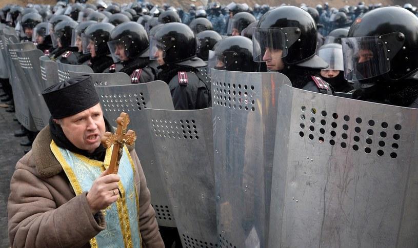 Duchowny przed oddziałem milicji /AFP