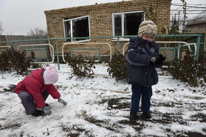Dzieci bawią się przed domem, w którym mieszkały. Budynek został zniszczony w czasie ostrzału /AFP