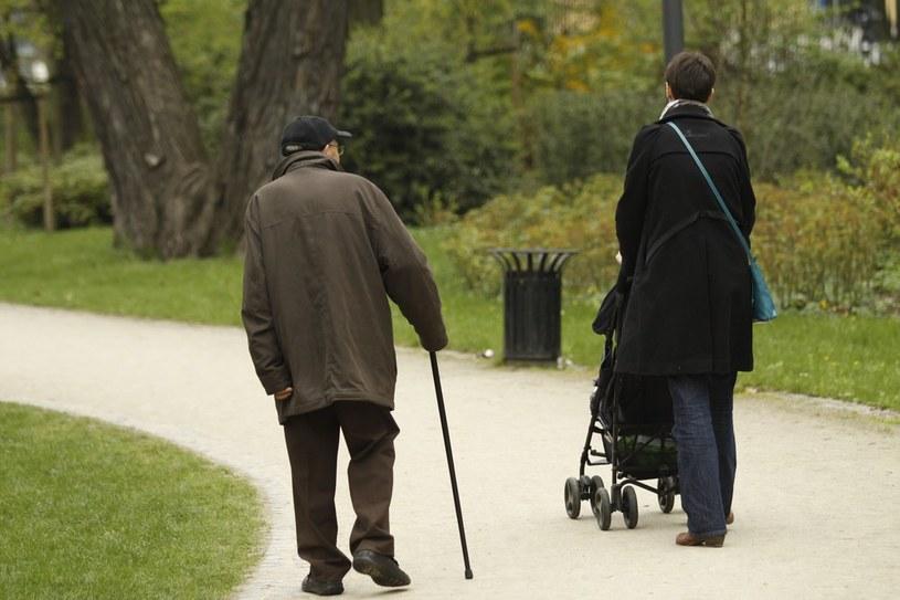 Emeryt i matka z dzieckiem spacerują po parku /Piotr Zając /Reporter