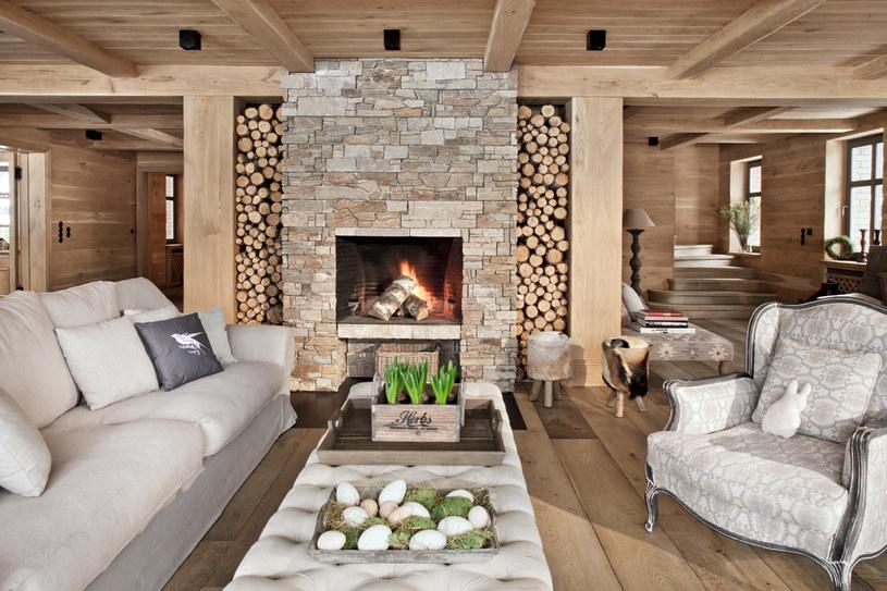 Fotel naprzeciw kominka zachęca do odpoczynku. Wszystkie meble są tapicerowane grubym, szlachetnym lnem, gładkim lub żakardowym. Miejsce do składowania drewna zostało wymyślone tak, żeby porządnie ułożone polana wyglądały jak ozdobna mozaika /Rafał Lipski /Twój Styl