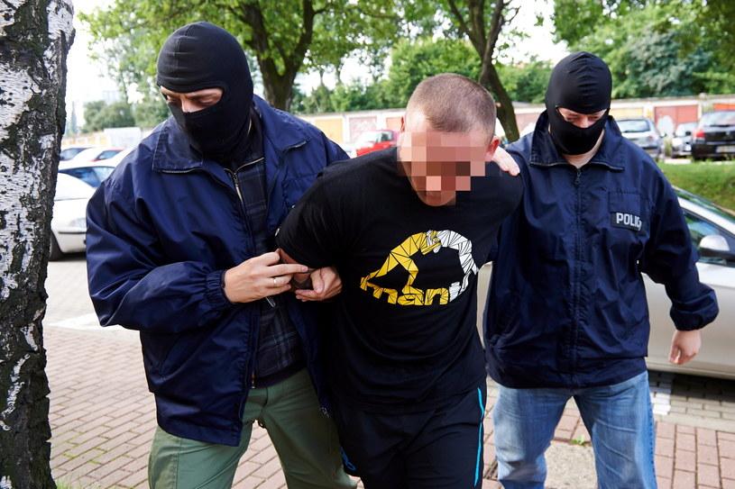 Funkcjonariusze policji prowadzą na przesłuchanie do Prokuratury Rejonowej w Gdyni jednego z kibiców /Adam Warżawa /PAP