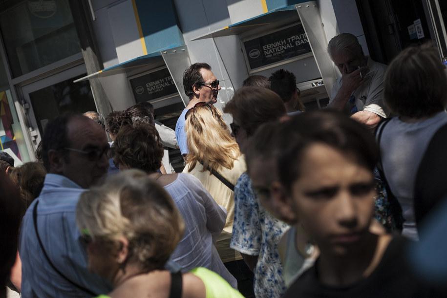 Grecy już w ubiegłym tygodniu ustawiali się w długich kolejkach do bankomatów. Teraz kolejki te są jeszcze dłuższe /Socrates Baltagiannis/dpa /PAP