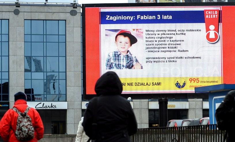 Informacja z systemu Child Alert o zaginięciu 3-letniego Fabiana, wyświetlana na ekranie reklamowym /Marcin Obara /PAP