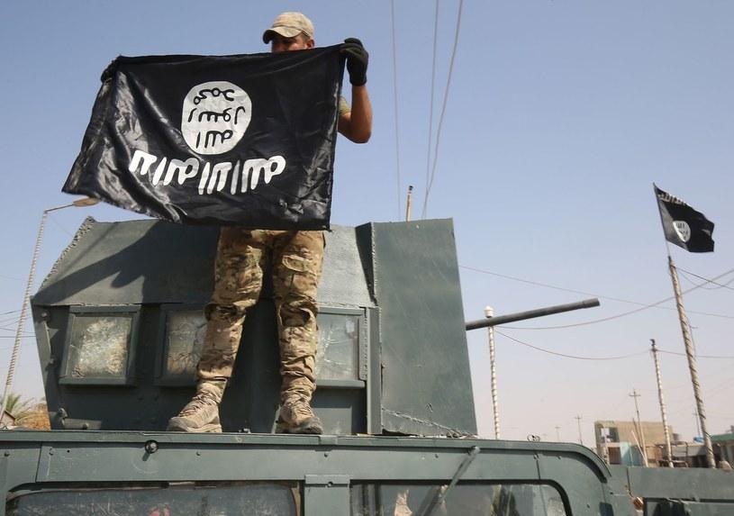 Irakijski żołnierz trzyma do góry nogami flagę tzw. Państwa Islamskiego, zdjęcie ilustracyjne /AFP