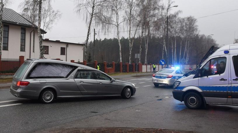 Karawan w asyście wozów policyjnych opuszcza cmentarz w Marysinie Wawerskim przy ul. Korkowej w Warszawie /Radek Pietruszka /PAP