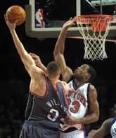 Knicks - Nets 96:114. Marcus Camby (z prawej) próbuje blokować rzut Aarona Williamsa