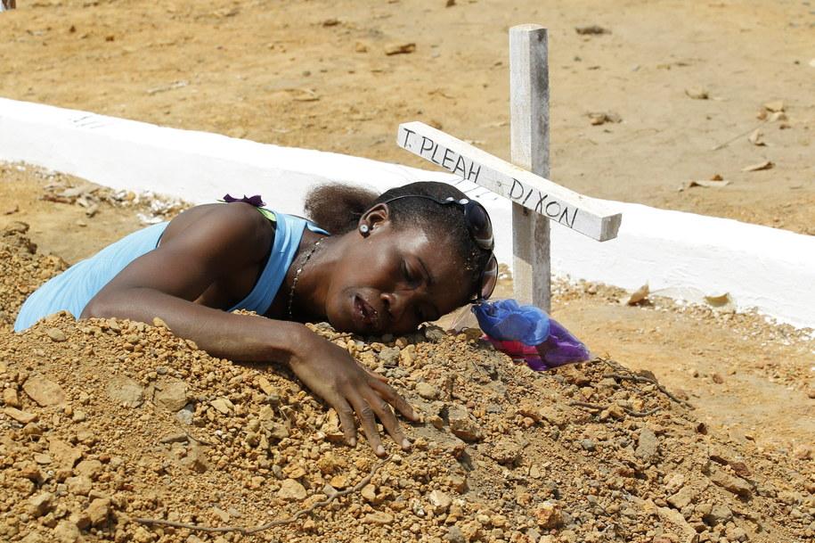 Kobieta na grobie jednej z ofiar eboli /AHMED JALLANZO  /PAP/EPA