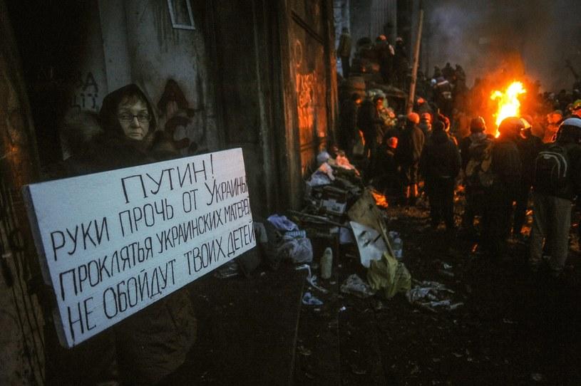 """Kobieta trzyma transparent: """"Putin! Ręce precz od Ukrainy!"""" /PAP/EPA"""