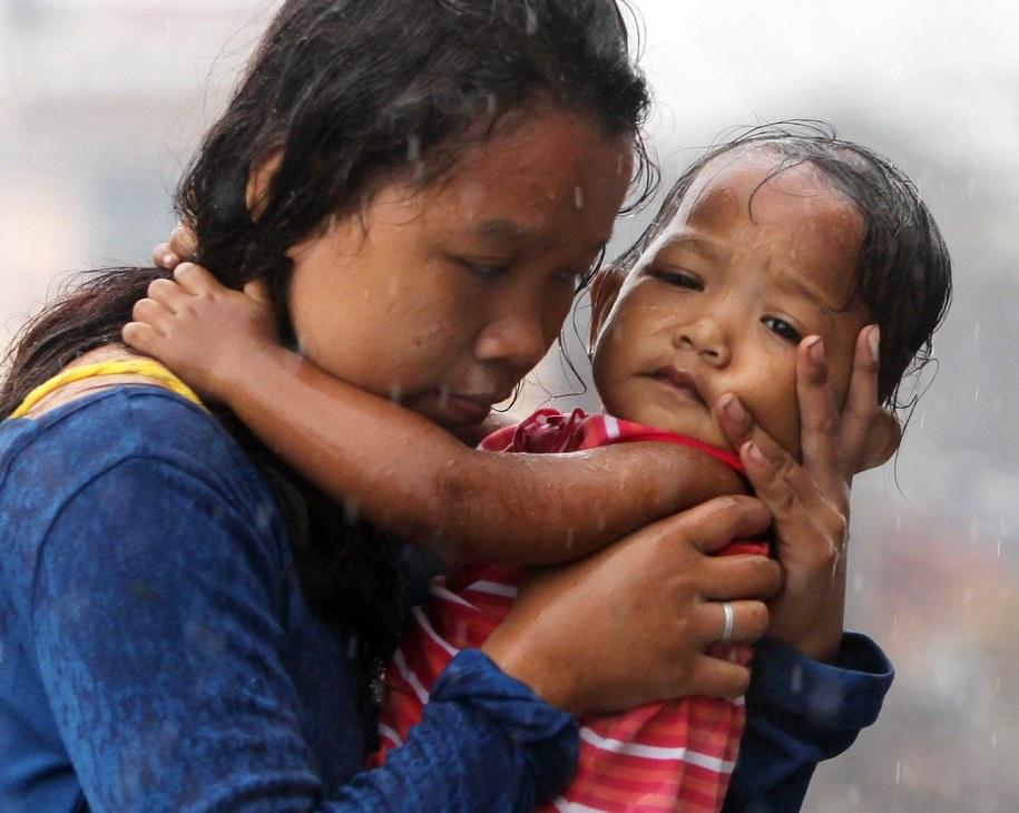 Kobieta trzymająca na rękach swoje dziecko /FRANCIS R. MALASIG /PAP/EPA
