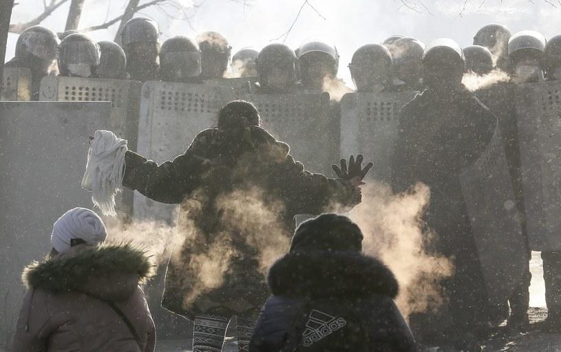 Kobiety klęczą przed oddziałem milicji /PAP/EPA
