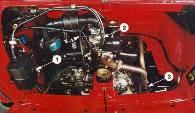 Komora silnika Fiata 126 z katalizatorem: 1 - węglowy pochłaniacz oparów paliwa, 2 - dodatkowy wężyk łączący podstawkę pod gaźnik z pochłaniaczem, 3 - zaślepione miejsce po planowanej sondzie lambda. /Motor