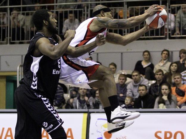 Koszykarz Polonii Darnell Hinson (P) łapie piłkę przed Chrisem Oakesem (L) z Energi Czarnych /AFP