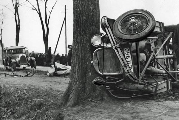 1936 r. Wypadek samochodowy na trasie Poznań-Żegrze. Skutki wypadku samochodowego. Widoczny zgnieciony rower, zwłoki przykryte papierem, w tle przewrócony samochód oraz przedstawiciele policji.