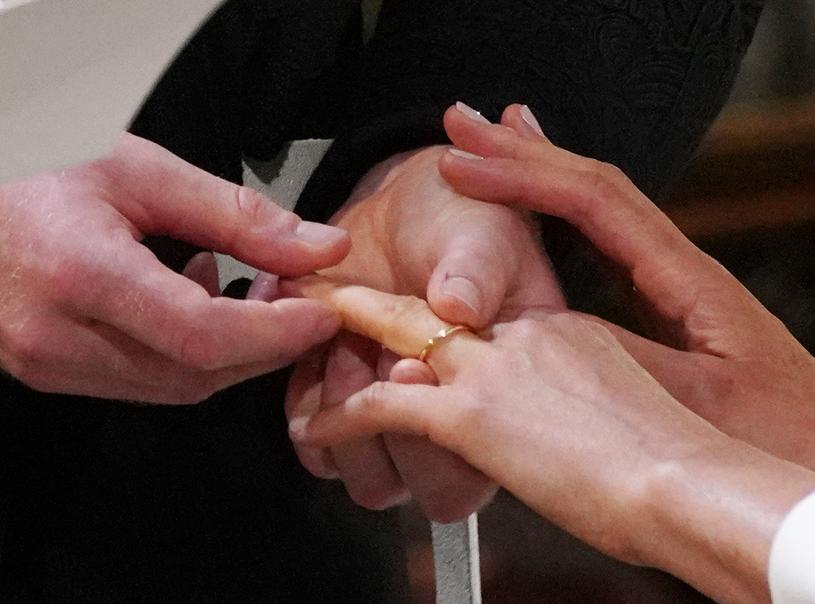 Książę Harry nakłada obrączkę Meghan Markle /AFP