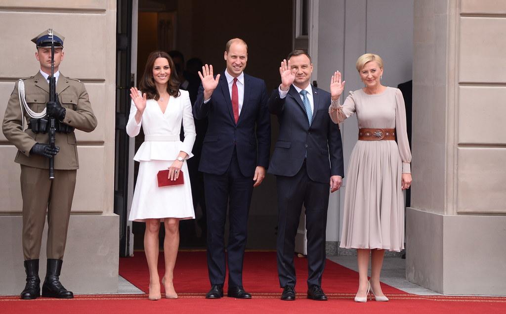 Księżna Kate ubrana jest w biały kostium i cieliste szpilki //PAP