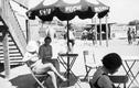 """Plażowicze w Krakowie podczas wypoczynku pod parasolem z napisem """"Pijcie mleko"""". W tle widoczna reklama z napisem """"Pijcie piwo Okocimskie"""" (zdjęcie z 1931 roku)"""