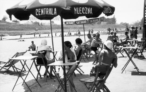 Plażowicze podczas wypoczynku przy stolikach pod parasolami. Plaża Towarzystwa Uniwersytetu Robotniczego w Krakowie (zdjęcie z 1931 roku)