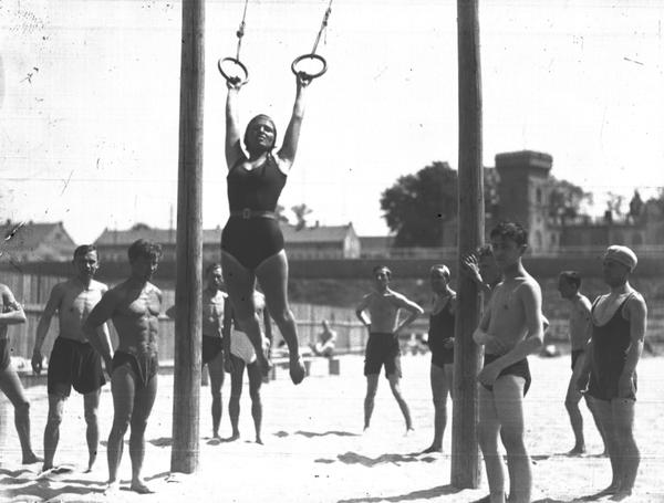 Kobieta na huśtawce oraz inni plażowicze podczas zabawy i wypoczynku. Plaża Towarzystwa Uniwersytetu Robotniczego w Krakowie (zdjęcie z 1931 roku)