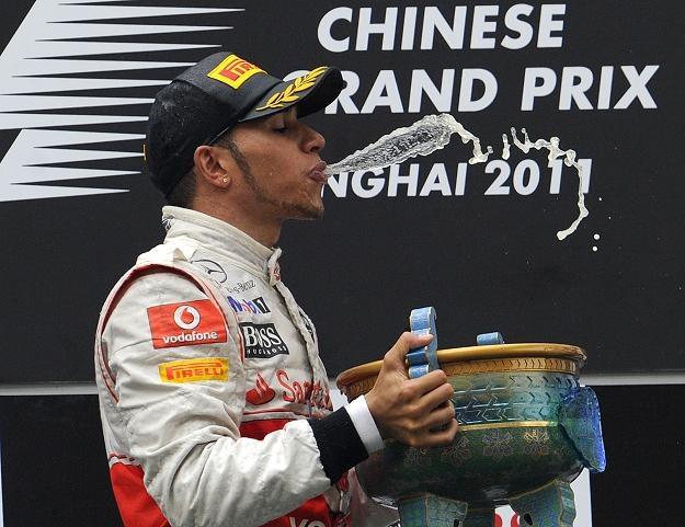 """Lewis Hamilton z radości po wygranej """"pluje"""" szampanem /AFP"""