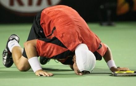 Lleyton Hewitt awansował po ciężkim boju i pocałował kort w Melbourne /AFP