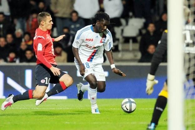 Ludovic Obraniak stara się zablokować piłkarza Lyonu Bafetimbiego Gomisa /AFP