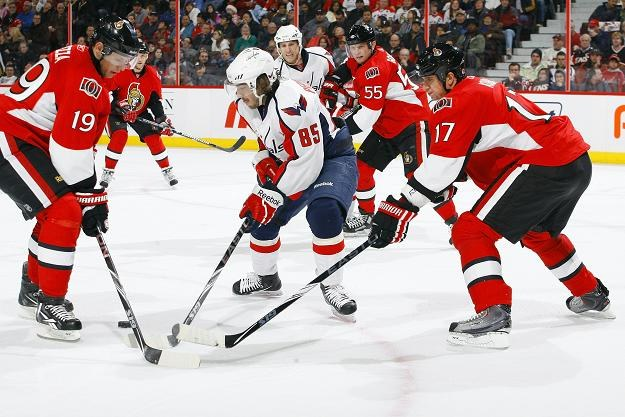 Mathieu Perreault (Washington Capitals) w walce z hokeistami Ottawa Senators /AFP