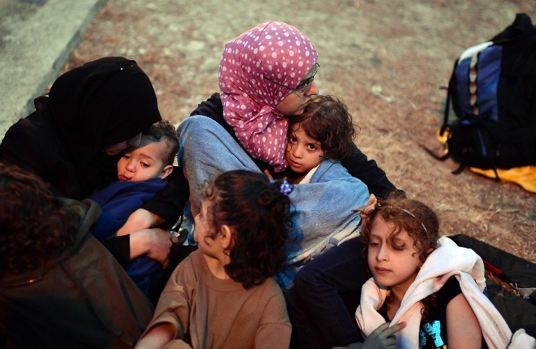 Matki próbują ogrzać swoje dzieci. To uchodźcy z Syrii, którzy koczują na greckiej plaży /LOUISA GOULIAMAKI / AFP /AFP
