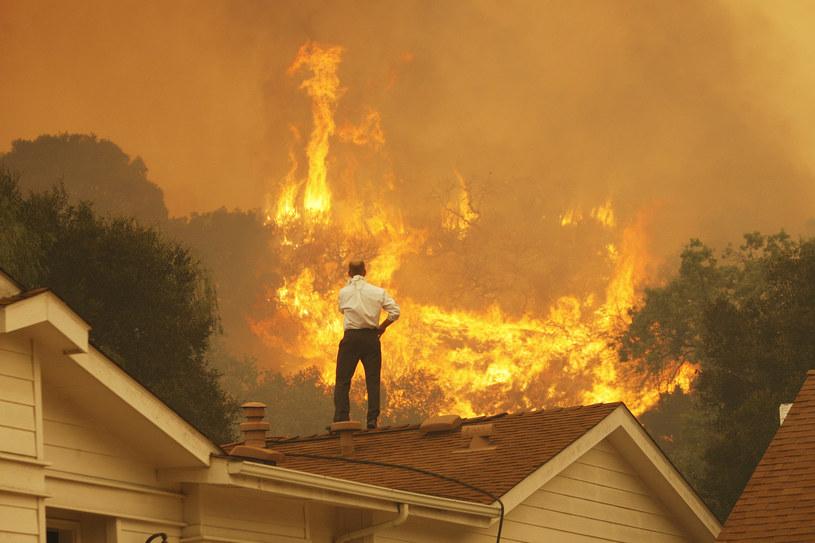 Mężczyzna na dachu swojego domu obserwuje pożar /David McNew /AFP/Getty